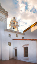 Sunset From A Church Courtyard With A Bell Tower. Cloudy Afternoon From Chapel Exterior With Bells. Serenity, Calmness And Serenity Concept.Religion Architecture