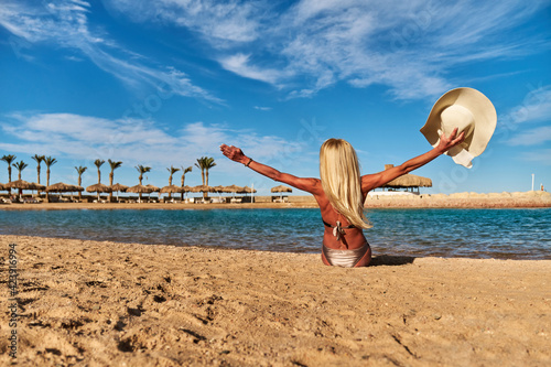 Young fashion woman sitting on the beach shore Wallpaper Mural