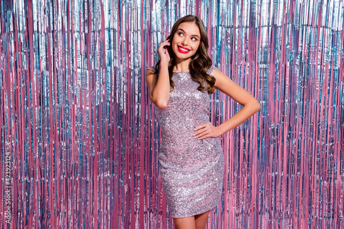 Fototapeta Portrait of attractive luxury cheerful curious wavy-haired girl clubber thinking isolated over glossy tinsel colorful curtain background obraz na płótnie