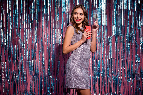 Fototapeta Photo of young woman happy smile party hold glass of champagne use cellphone look empty space isolated over glitter color background obraz na płótnie
