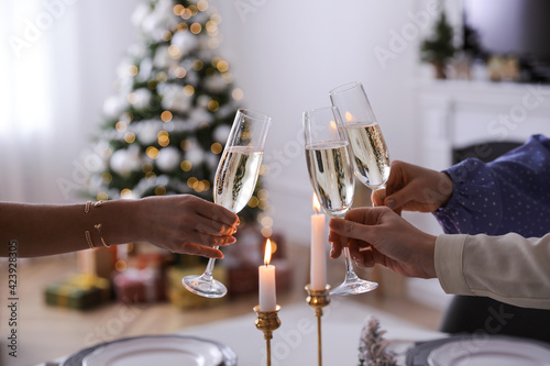 Fotografia People clinking glasses with champagne at home, closeup