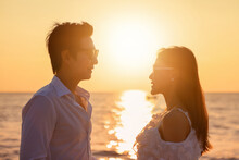 Young Happy Asian Couple Looks At Each Other On The Beach, Romantic Travel Honeymoon Vacation Summer Holidays. Asian Woman And Man Holding Hands Embracing Outdoors On Sunset Background.