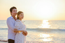 Young Happy Asian Couple Hug On The Beach, Romantic Travel Honeymoon Vacation Summer Holidays. Asian Woman And Man Holding Hands Embracing Outdoors On Sunset Background