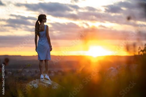 Tela A young woman in summer dress standing outdoors enjoying view of bright yellow sunset
