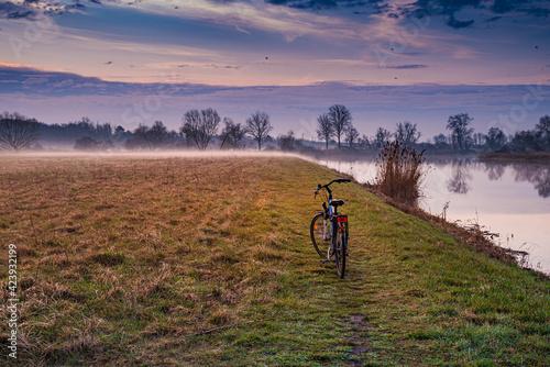 rower nad brzegiem rzeki - fototapety na wymiar