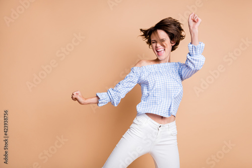 Photo of young excited crazy girl happy positive smile rejoice win victory fists hands isolated over beige color background