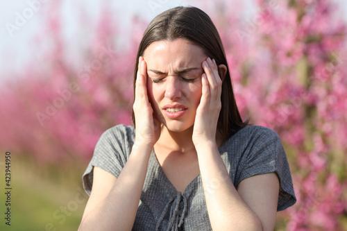 Obraz Woman suffering migraine in a flowered field - fototapety do salonu