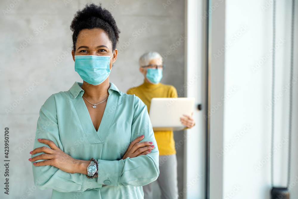 Fototapeta Business people wearing masks and social distancing in office