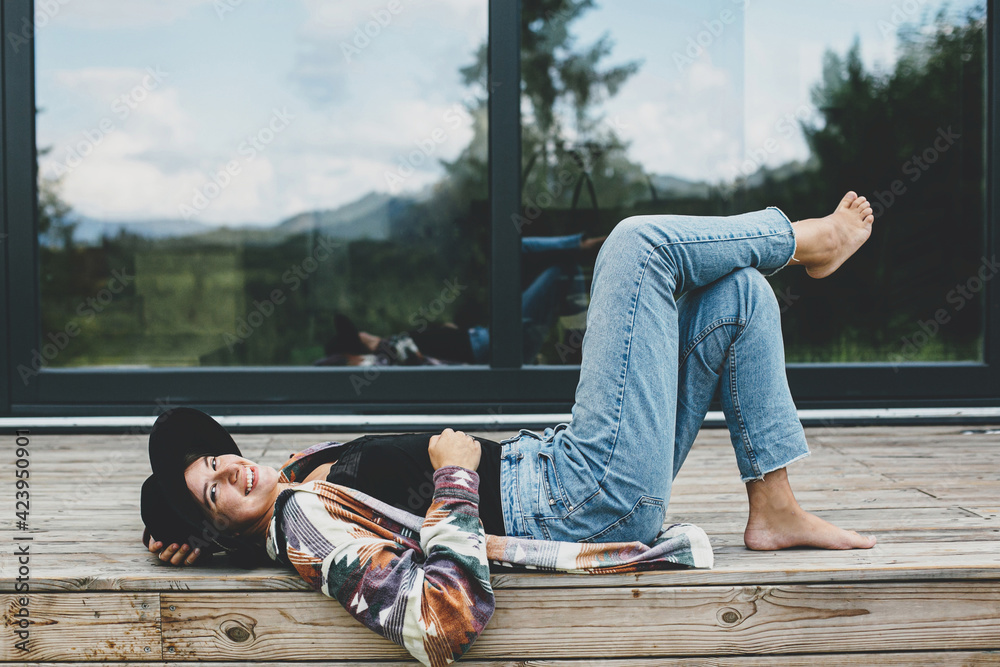 Fototapeta Stylish happy woman relaxing on wooden terrace at modern cabin with windows in mountains. Travel - obraz na płótnie