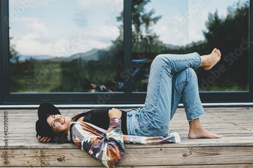 Papel de parede Stylish happy woman relaxing on wooden terrace at modern cabin with windows in mountains