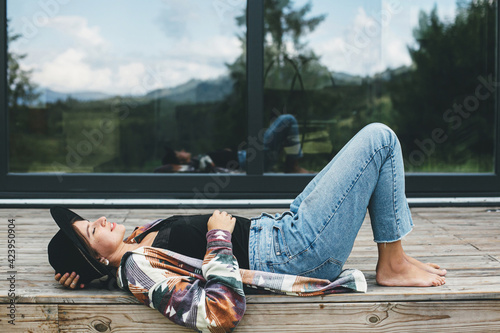 Fototapeta Stylish happy woman relaxing on wooden terrace at modern cabin with windows in mountains. Travel obraz na płótnie