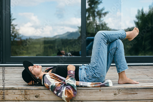 Fototapeta Stylish happy woman relaxing on wooden terrace on background of modern cabin in mountains. Tranquil obraz na płótnie