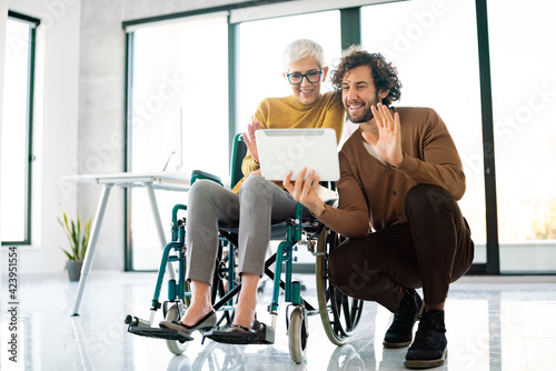 Business people with disability in whellchair working together in office