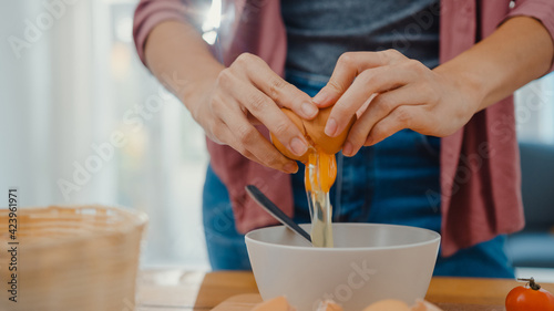 Fotografia Hands of young Asian woman chef cracking eggs into ceramic bowl cooking omelette with vegetables on wooden board on kitchen table in house