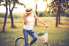 Beautiful Smiling Girl In Straw Hat With Bicycle In Park