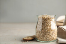 Jar And Wooden Spoon With White Quinoa On Light Grey Table. Space For Text