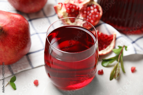 Glass of pomegranate juice and fresh fruits on white table