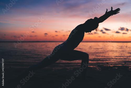 Photo Silhouette of slim female athlete with perfect body shape training flexibility o