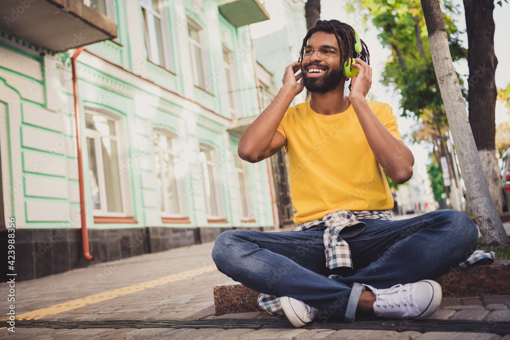 Fototapeta Photo portrait of guy sitting on the ground enjoying music smiling on city street in summer wearing casual outfit glasses - obraz na płótnie