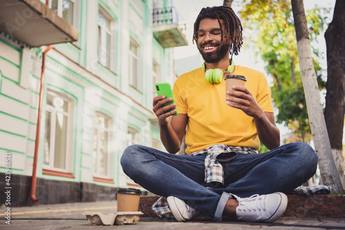 Fototapeta Photo portrait of young guy sitting on the ground reading news from smartphone drinking beverage wearing earphones spectacles obraz na płótnie