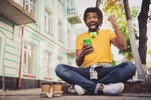 Fototapeta Photo portrait of young guy sitting on the ground keeping cellphone gesturing like winner wearing headphones glasses obraz na płótnie