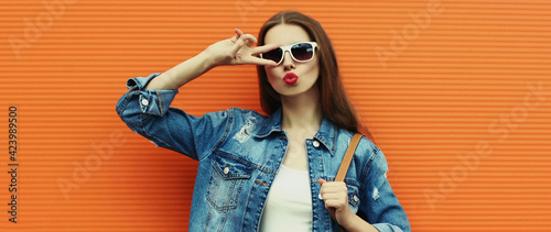 Obraz na plátne Portrait close up of young woman wearing a denim jacket with backpack posing on