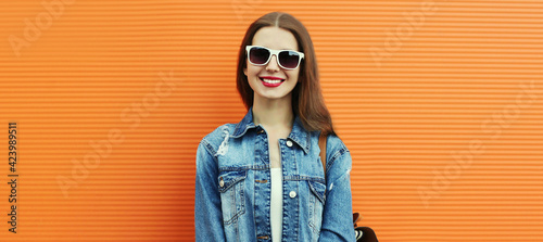 Fototapeta Portrait of happy smiling young woman wearing a denim jacket with backpack on a orange background obraz