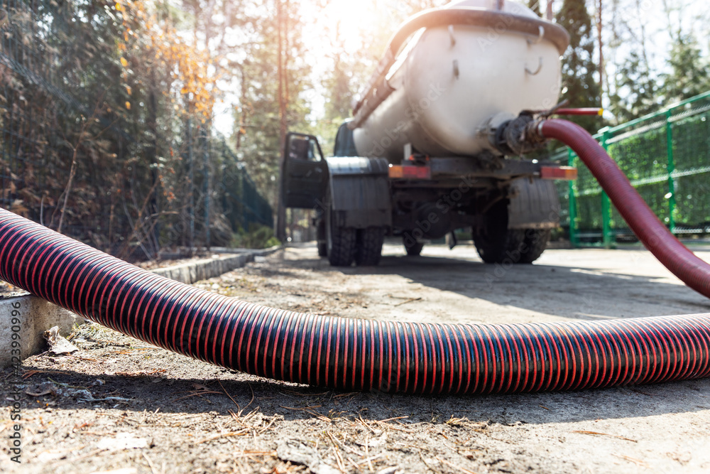 Fototapeta Close-up pipe hose of sewage truck car engine emptying home sewerage tank. Septic cleaning vacuum service and maintenance suburban countryside home. Suction vehicle cleaner machine pumping drainage