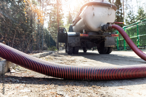 Fotografie, Obraz Close-up pipe hose of sewage truck car engine emptying home sewerage tank