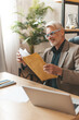 Positive judgment. Senior man opens a mailing letter with a smile. An experienced lawyer won the trial.