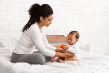 Black Mother Playing With Baby Giving Toy Sitting In Bedroom