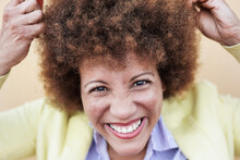 Trendy Latin Woman Touching Her Afro Hairs And Looking In Camera