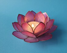 Pink Lotus Candle Holder With Burning Tealight Against A Blue Background