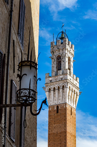 Photo Clock bell tower of  Siena, Tuscany, Italy with a small observation deck, blue s