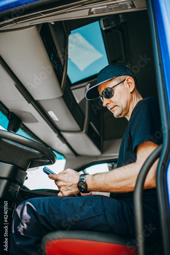Obraz Experienced truck driver sitting in his truck and waiting for a new driving route. - fototapety do salonu