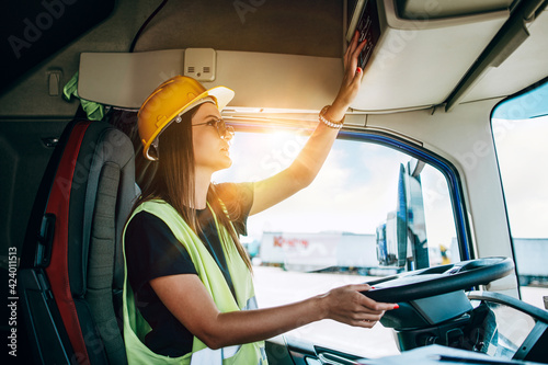 Obraz Portrait of beautiful young woman professional truck driver with protective yellow helmet sitting and driving a big truck. Inside of vehicle. People and industrial transportation concept. - fototapety do salonu