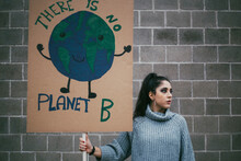 Female Activist Looking Away While Holding Planet Earth Poster Against Wall