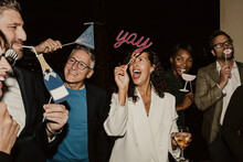 Cheerful Business People Enjoying With Props During Company Party At Night