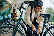 Female Student Unlocking Bicycle At Parking Station In College Campus
