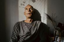 Depressed Senior Man Against Wall At Home