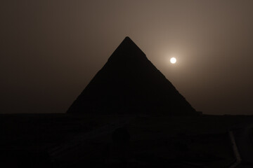View of the pyramid of Khafre, one of the three ancient Egyptian pyramids of Giza, during a sandstorm with the setting sun conveying a mystical experience