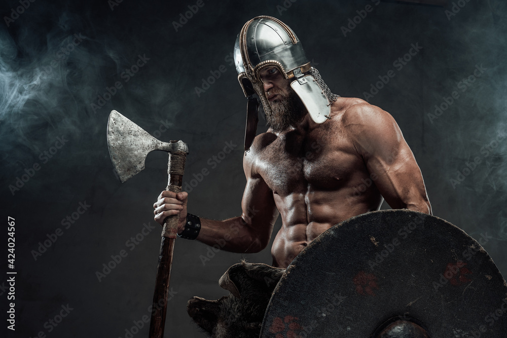Fototapeta Armoured and naked viking posing with axe and shield in smoke