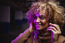 Smiling Hip Hop Girl Standing In Underground Garage And Putting Earphones To Listen To The Music.