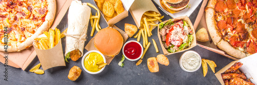 Fototapeta Delivery fastfood ordering food online concept. Large set of assorted take out foods pizza, french fries, fried chicken nuggets, burgers, salads, chicken wings, sides, black concrete background obraz