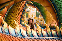 Happy Asian Woman Smiling In Colorful Serpent Statue At Wat Phra That Nong Bua Temple