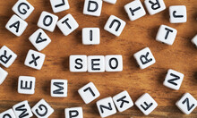 Small White And Black Bead Cubes On Wooden Board, Letters In Middle Spell SEO - Search Engine Optimization Concept