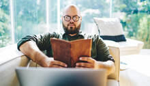 Serious Man Reading Novel Relaxing On Sofa