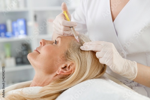 Papel de parede Cosmetologist does prp therapy against hair loss of a senior blond woman in a beauty salon