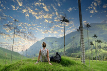 Girl With Backpack Sitting On Green Grass Watching Gigantic Palm Trees In Cocora Valley In Colombia