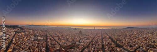 Fotografia Aerial panorama drone shot of Barcelona with sunrise over sea horizon in Spain w